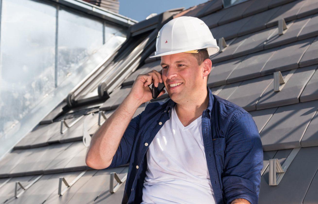 Dachdecker mit Mobiltelefon