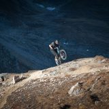 Cyclist performing a stunt next to a steep cliff in the mountains.