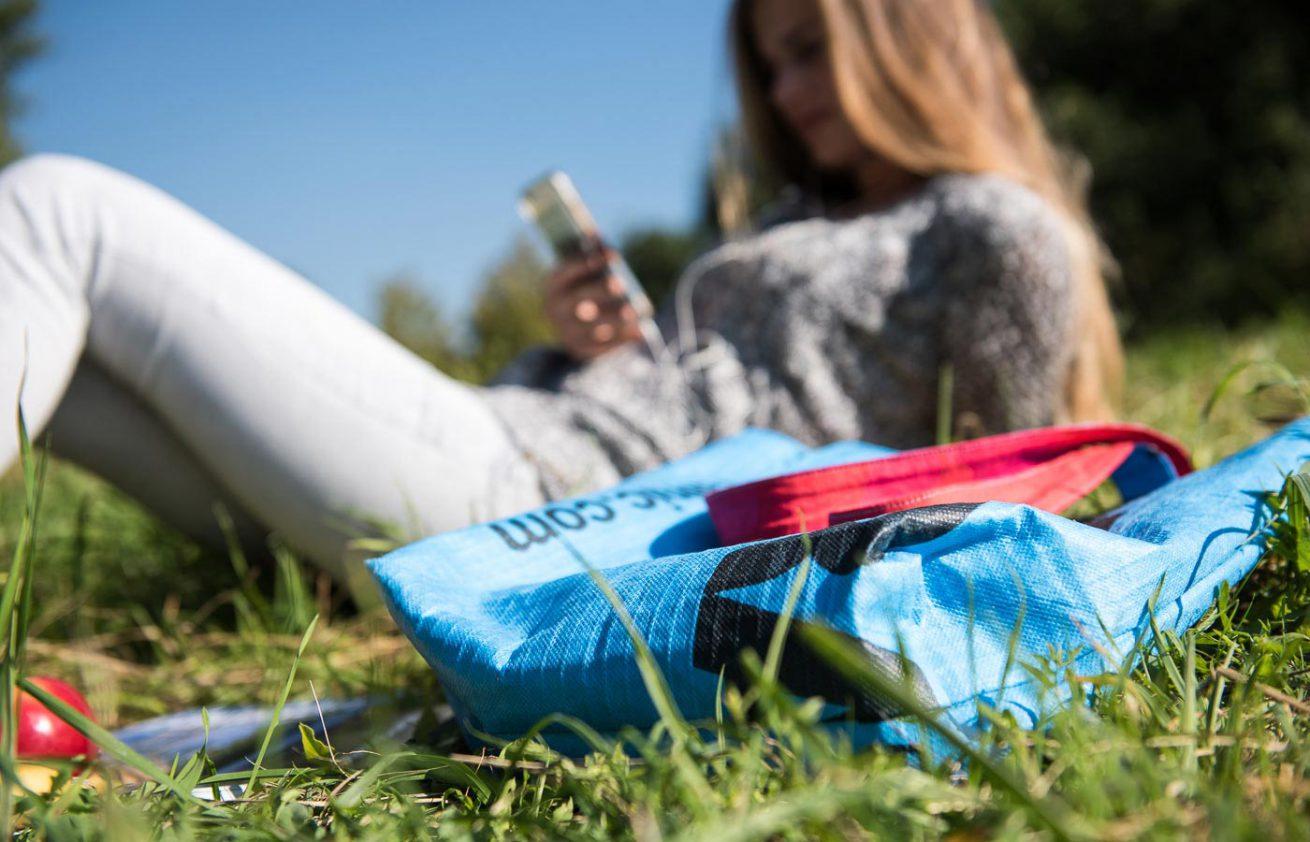 Junge Frau im Gras mit Strandtasche und Mobiltelefon