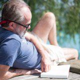 Mann liest Buch am Seeufer