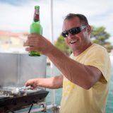 Mann mit Bierflasche am Grill