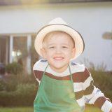 Lachendes Kind mit Hut im Garten