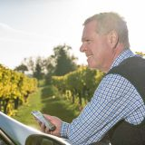Winzer im Weingarten mit Mobiltelefon