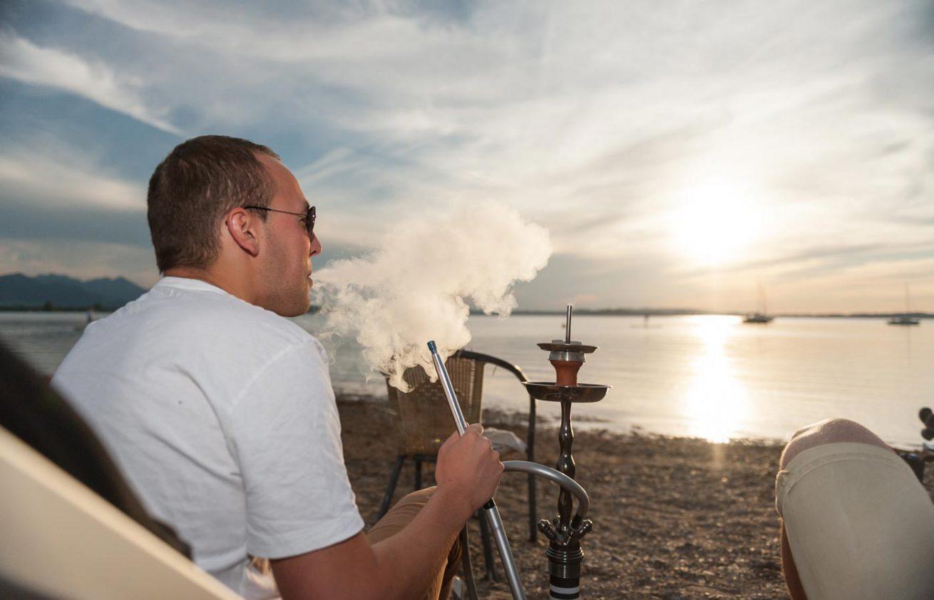 Mann mit Shisha am Seeufer