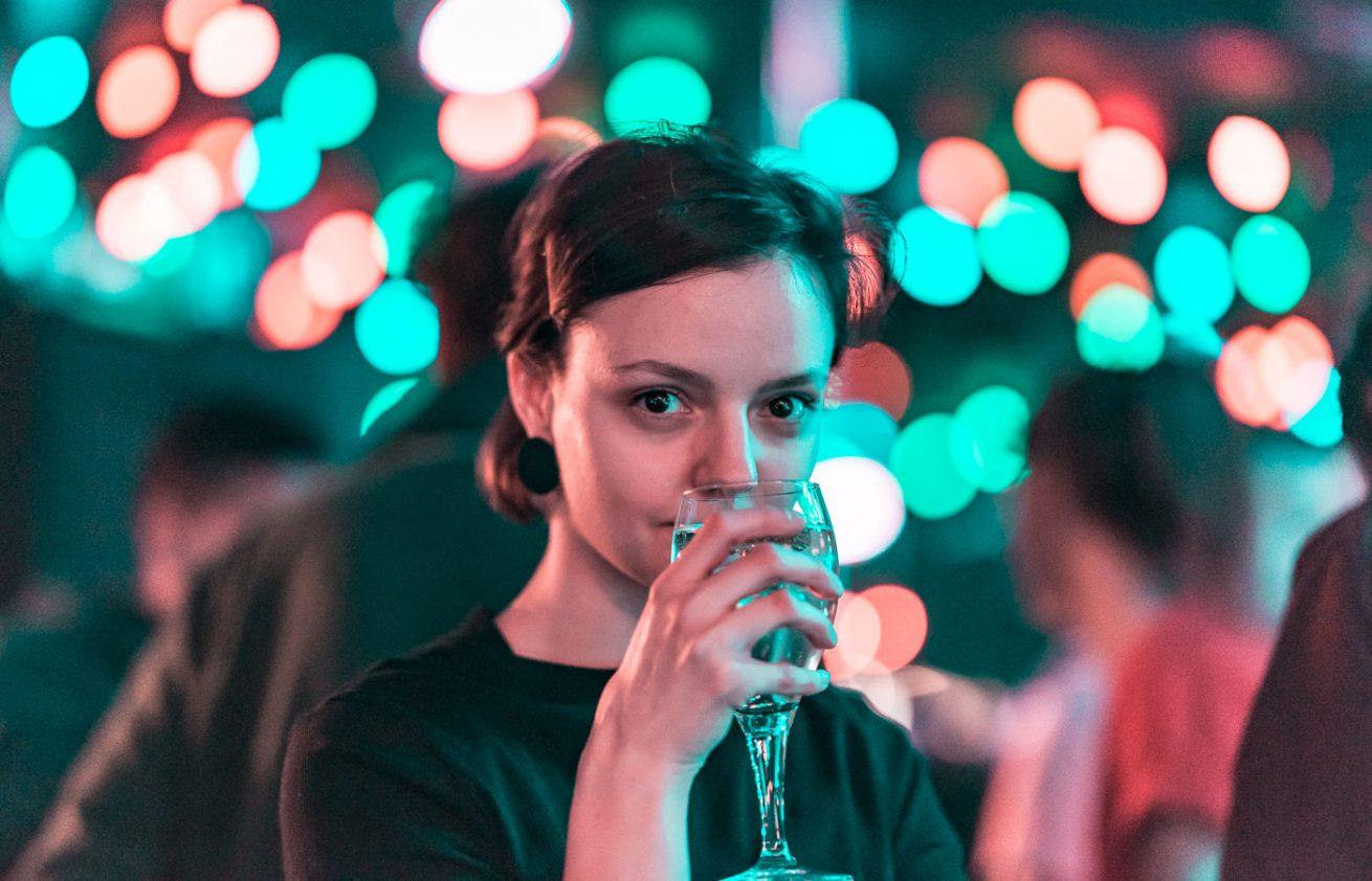 Woman in bar drinking glass of wine